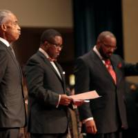 The Rev. Al Sharpton (left) attends the fMonday uneral services for 18-year-old Michael Brown at Friendly Temple Missionary Baptist Church in St. Louis. Hundreds of people gathered to say goodbye to Brown, who was shot and killed by a Ferguson, Missouri, police officer on Aug. 9. At center is church Pastor Michael Jones and at right is Pastor Charles Ewing, an uncle of Michael Brown. | AP