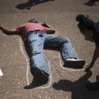 An activist outlines a man lying in front of City Hall in St. Louis on Tuesday. | REUTERS