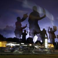 This long-exposure photo shows protesters marching in the street Wednesday in Ferguson, Missouri, as lightning flashes in the distance. | AP