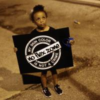 A girl holds a sign Thursday during protests over the shooting of unarmed black teen Michael Brown in Ferguson, Missouri.   AFP-JIJI