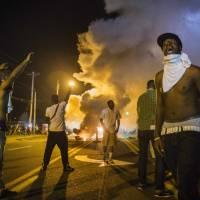 Police fire tear gas near Ferguson, Missouri, in an attempt to disperse protesters as violent unrest continued Monday in reaction to the shooting of an unarmed local black teenager, Michael Brown. | REUTERS