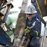 A roughneck wrestles the ring of wedges locking the drill shaft on a gas well rig for Encana Corp. near the Canadian village of Alix, in December 2009. Encana invested $2 million to refrack two wells in Louisiana's Haynesville shale formation earlier this year. | BLOOMBERG