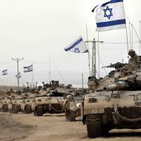 Israeli Merkava tanks pass near the border with the Gaza Strip on their way back from the Palestinian coastal enclave on Tuesday. | AFP-JIJI