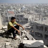 A Palestinian looks at the destruction in Gaza City's al-Tufah neighborhood as a fragile cease-fire between Israel and Hamas, which governs the Gaza Strip, entered a second day on Wednesday. Israel's military invasion has killed nearly 1,900 Palestinians, mostly civilians, while over 60 have died on the Israeli side, the majority of them soldiers. | AFP-JIJI