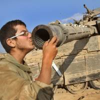 An Israeli soldier kisses the barrel of his Merkava tank along the border with the Gaza Strip on Sunday. | AFP-JIJI