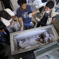 Dead Palestinian children lie in a freezer after an Israeli airstrike Sunday on a residential home in Rafah, the Gaza Strip. | REUTERS