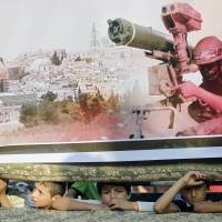 Palestinian boys look on from behind a stage where a giant poster showing a Hamas fighter is displayed during a demonstration Sunday in the southern town of Rafah in the Gaza Strip.  | AFP-JIJI
