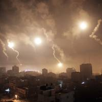 Flares shot by Israeli forces light up the night sky over Gaza City, in the Gaza Strip, early Tuesday. | AP