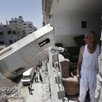 A Palestinian inspects the damage to his home after a minaret from neighboring Al-Sousi Mosque fell on it after it was destroyed in an Israel strike on Shati refugee camp, in the northern Gaza Strip, on  Wednesday. | AP