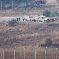 A picture taken from the Israeli-occupied Golan Heights shows armed men, reportedly rebel fighters, standing near vehicles in the Syrian side, near the Quneitra border crossing, on Thursday. Israel closed off the area around Quneitra the previous day after an officer was wounded by stray fire as Syrian rebels seized control of the crossing. | AFP-JIJI