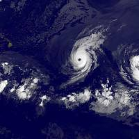 A NASA satellite photo Tuesday shows Hurricane Iselle(center) in the Eastern Pacific Ocean near the Hawaiian islands (left). Iselle, now a category 4 hurricane, barreled toward Hawaii early Tuesday, with forecasters warning that the islands could face a one-two punch as Tropical Storm Julio (right) is trailing not far behind. | AFP-JIJI