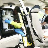A woman watches as her husband buckles up the anthropomorphic robot named hitchBot after picking it up outside of Halifax, Nova Scotia, on Wednesday. | REUTERS