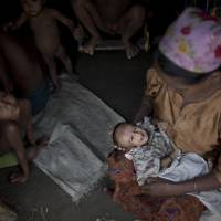 Roshida Beugam cradles her 3-month-old child, who already has signs of malnutrition, at her family's makeshift tent in a camp for Rohingya north of Sittwe in Myanmar, on June 25.   AP