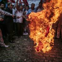 Uighurs living in Turkey set on fire a representation of a Chinese flag outside the Chinese Consulate in Istanbul on Saturday as they stage a protest to condemn the killings of Uighurs allegedly killed in China's Xinjiang Uighur Autonomous Region. | AP