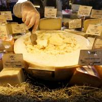 A worker arranges cheese for sale at a grocery store in St. Petersburg on Monday. Moscow initially said it would not stoop to a tit-for-tat response to newly imposed sanctions, but last week it took aim at Western food imports. | REUTERS