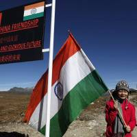 An Indian girl poses with an Indian flag at the border with China in Bumla, Arunachal Pradesh state, in October 2012. | AP