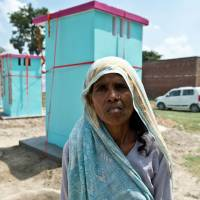 Dhanwati Devi, who lives in Katra Shahadatganj village in Uttar Pradesh state, stands in front of newly-built toilets donated by sanitation charity Sulabh International in her village on Sunday. More than 100 toilets were erected in the poverty-stricken and scandal-hit village in northern India, where fearful and vulnerable women have long been forced to defecate in the open. | AFP-JIJI