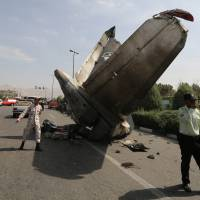 Iranian Revolutionary Guards and security forces stand next to the remains of a plane that crashed near Tehran's Mehrabad airport on Sunday. | AFP-JIJI