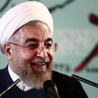 Iranian President Hassan Rouhani  smiles during a press conference in Tehran on Saturday. Iran accused the United States of duplicity for imposing new sanctions on organisations linked to Tehran's nuclear program, despite long-running but active negotiations to end the standoff.   AFP-JIJI