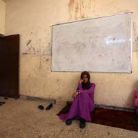Iraqi Yazidi women who fled the violence in the northern Iraqi town of Sinjar, sit at a school where they are taking shelter in the Kurdish city of Dohuk in Iraq's autonomous Kurdistan region, on Tuesday. | AFP-JIJI