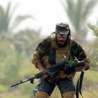 A Shiite Muslim fighter from the Peace Brigades, a group that was formed by Iraqi cleric Muqtada al-Sadr to defend Shiite holy sites, takes position Monday south of Baghdad on the Jurf al-Sakhr front line, the scene of heavy fighting against advancing jihadist militants and Islamic State fighters. | AFP-JIJI