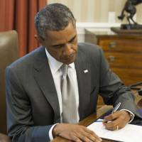 U.S. President Barack Obama signs a bill providing $225 million in supplemental emergency funding to Israel for the Iron Dome missile defense system, in the Oval Office of the White House in Washington on Monday. | AFP-JIJI