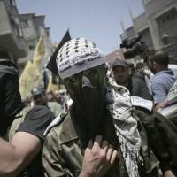 A masked militant wears a headband with Arabic writing which reads, 'The martyr, Abdul Qader al-Husaini brigades,' during the funeral service for two Fatah militants killed by an Israeli airstrike at Bureij refugee camp, in the central Gaza Strip, on July 7. | AP