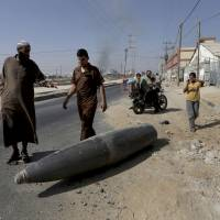 Palestinian onlookers and motorists pause to inspect a bomb from the Israeli military lying unexploded on the main road in Deir el-Balah in the central Gaza Strip on  Friday. | AP