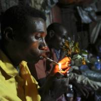 Somali men smoke and chew khat, a narcotic shrub that is grown in the highlands of Kenya and Ethiopia and is popular across the Horn of Africa and Yemen, inside a makeshift building in Mogadishu on Aug. 6. | REUTERS