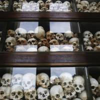 Skulls are stacked up behind glass at a memorial stupa made with the bones of victims of the Khmer Rouge regime at Choeung Ek, a 'Killing Fields' site on the outskirts of Phnom Penh, on Wednesday. Two former Khmer Rouge leaders were convicted Thursday for crimes against humanity by a U.N.-backed tribunal. | REUTERS