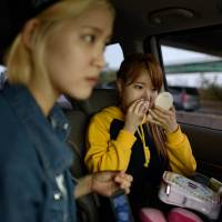 Betty (right), a member of K-pop group Billion, checks her makeup as the group travels from their rehearsal studio to a stylist in Seoul on June 10. | AFP-JIJI