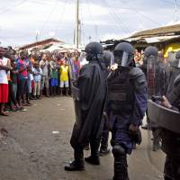 Liberian security officers dressed in riot gear (right) control a crowd of people in the West Point slum as the government enforces a quarantine aimed at containing the deadly Ebola virus in Monrovia, Liberia, on Wednesday. | AP