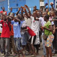 People who live near the West Point Ebola center in Monrovia protest as they are not allowed to enter the area leading to their homes, after Liberia security forces blocked roads amid a government clampdown on the movement of people to prevent the spread of the virus Wednesday. Security forces deployed to enforce a quarantine around a slum. | AP