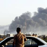 Smoke billows across the sky after a gasoline depot was set ablaze during clashes between rival militias near Tripoli's international airport on Wednesday. | AFP-JIJI