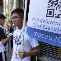 A man votes on a tablet device next to a volunteer with a banner promoting an informal civil referendum which took place in Macau last Sunday. | AP