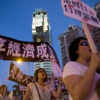 Gaming workers protest outside Casino Grand Lisboa in Macau on Monday. | BLOOMBERG