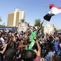 Iraqis chant pro-government slogans and wave national flags in a show of support for embattled Prime Minister Nouri al-Maliki during a demonstration in Baghdad, in Iraq, on Monday.   AP