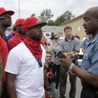 Missouri Highway Patrol Capt. Ron Johnson (right) talks to men Friday outside a market where teenager Michael Brown reportedly stole cigars before being killed by police. | AP