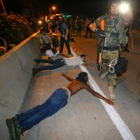 Police arrest dozens of protesters after some began throwing objects at officers in Ferguson, Missouri, early Wednesday as violent demonstrations continued over the fatal shooting of unarmed black teenager Michael Brown by a policeman. | AP