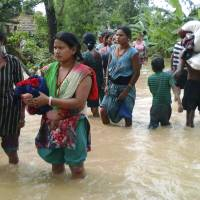 Nepalese villagers carry their belongings while wading through a flooded street in Bardia, western Nepal, on Friday. | AP