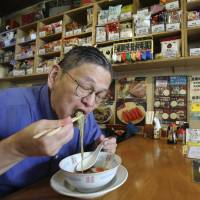 Instant ramen expert Masaya Oyama slurps noodles at a shop and restaurant that specializes in instant noodles in Tokyo on Tuesday. | AP