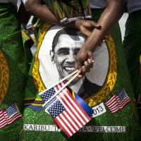 Women from a welcoming group wearing skirts and shawls printed with the face of U.S. President Barack Obama gather at Julius Nyerere Airport at the end of his Africa trip in July 2013, at Dar es Salaam, Tanzania. Obama is gathering nearly 50 African heads of state in Washington for a summit to help build his legacy on a continent where his commitment has been questioned. | AP