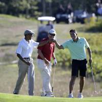 President Barack Obama bumps fists with Cyrus Walker, cousin of White House senior adviser Valerie Jarrett, as Glenn Hutchins looks on while golfing Thursday at Vineyard Golf Club in Edgartown on the Massachusetts island of Martha's Vineyard. | AP