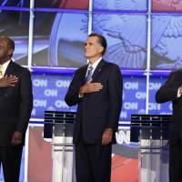 Texas Gov. Rick Perry (right) stands with fellow presidential candidates Herman Cain (left) and former Massachusetts Gov. Mitt Romney before a Republican presidential debate in Las Vegas in October 2011. | AP