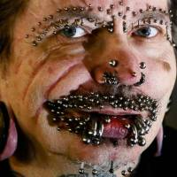 German Rolf Buchholz shows his face with 168 piercings Saturday as he visits the 20th Tattoo Convention in Berlin. A Dubai nightclub that hoped to feature Buchholz, who holds the world record for having the most piercings, said in an emailed statement Sunday that he was refused entry to the gulf city because of security concerns. | AP