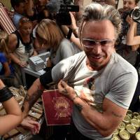 U.S. actor Mickey Rourke stands in front of journalists as he wears a T-shirt with the portrait of Russian President Vladimir Putin in central Moscow on Monday. The sale of a new collection of T-shirts with Putin's portrait starts the same day in the city at a price of 1,200 rubles (€25). | AFP-JIJI