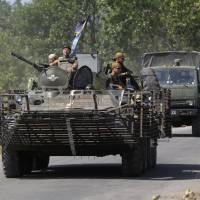 A Ukrainian military convoy moves along a road near Donetsk on Saturday. Ukraine said the same day it had headed off an attempt by Russia to send troops into Ukraine under the guise of peacekeepers with the aim of provoking a large-scale military conflict, a statement Moscow dismissed as a 'fairy tale.' | REUTERS