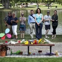 People pause by a bench Tuesday at Boston's Public Garden, where a small memorial has sprung up at the place where Robin Williams filmed a scene during the movie 'Good Will Hunting.' Williams, 63, died at his San Francisco Bay Area home Monday in an apparent suicide. | AP