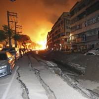 Tossed vehicles line an destroyed street as flames continue to burn from multiple explosions from an underground gas leak in Kaohsiung, Taiwan, early Friday. | AP