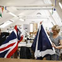 Workers fold a hand-sewn Union flag (left) and a Scottish St. Andrew's or Saltire flag after they were made at Specialised Canvas Services, Ltd., in Chesham, northwest of London, on Aug. 1. | BLOOMBERG
